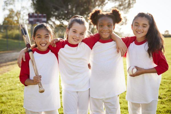 Schoolgirl baseball team holding baseball, portrait