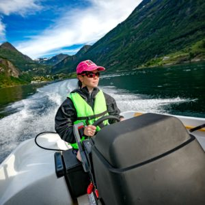 Woman driving a motor boat. Geiranger fjord, Beautiful Nature No