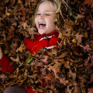 Little girl laying in a pile of fallen raked leaves