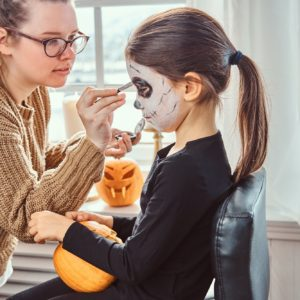 Mom painting daughter face for Halloween party.