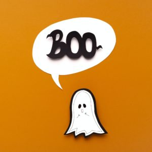 Scary ghost saying boo on orange Halloween background