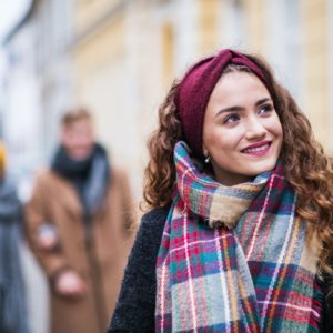 A portrait of teenage girl with headband and scarf on the street in winter.