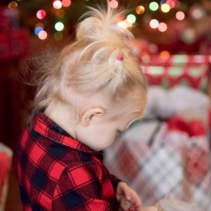 Little girl opening presents on Christmas Day in buffalo plaid pajamas