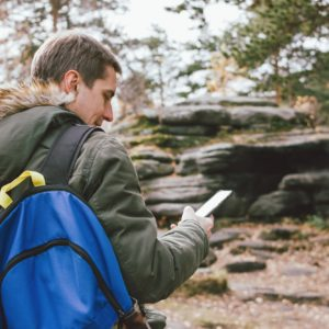Young male traveler in khaki parka jacket with backpack looks at the route in his mobile phone