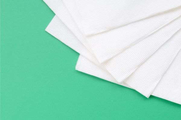 Several white paper napkins lie on a plastic green background
